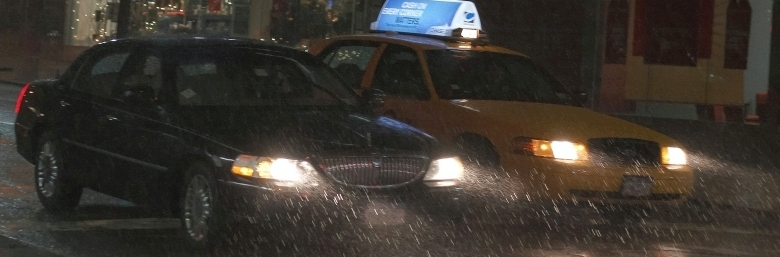 A rainy nightime view of a towncar and a taxicab stopped side by side at a crosswalk with their headlights beaming into the raindrops. Photo courtesy of: Digiart2001 | jason.kuffer | Flickr