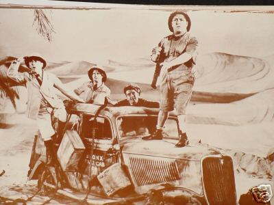 Movie still picture of the Three Stooges and a 1940s taxi in the desert