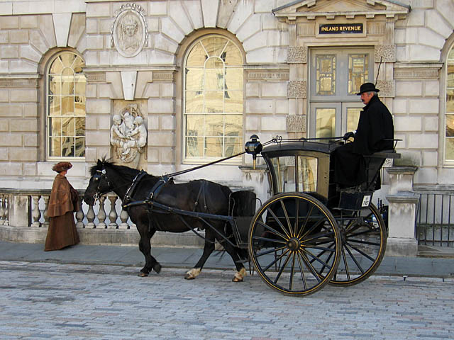 A horse drawn hansom cab with the driver riding high up in the rear of the carriage