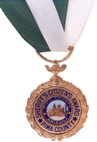 A gold-colored medal is suspended beneath a green and white ribbon