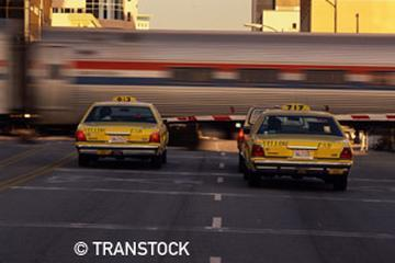 Taxis wait at a crossing as an Amtrak train passes
