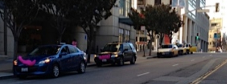 Two Lyft vehicles wait for fares at a San Francisco hotel
