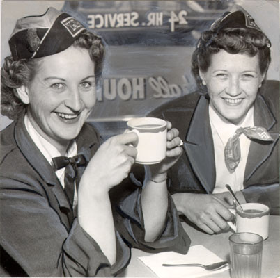 Uniformed women cab drivers enjoy cups of a hot beverage