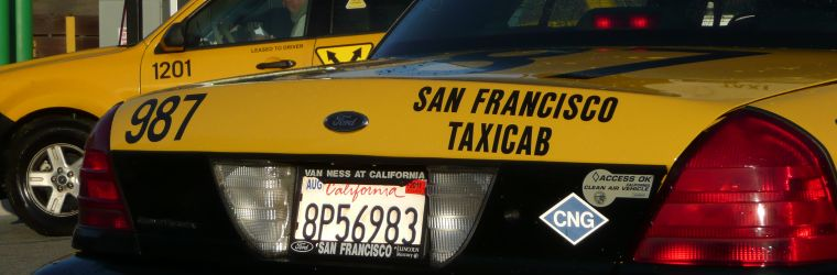View of signage on two cabs at a San Francisco taxi company. Photo by Charles Rathbone