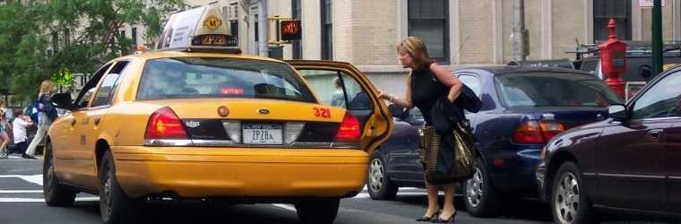 A woman passenger is opening the door of a taxi on a busy New York City street