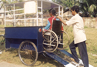 A bicycle rickshaw driver assists a woman passenger up a ramp and into the open-air passenger compartment