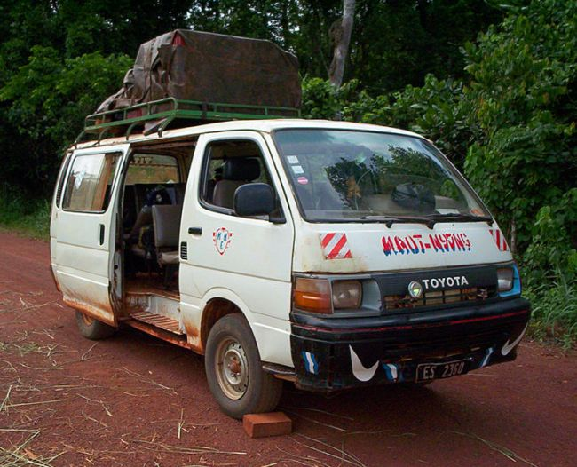 A full cargo rack sits atop a minivan taxi on an unpaved road