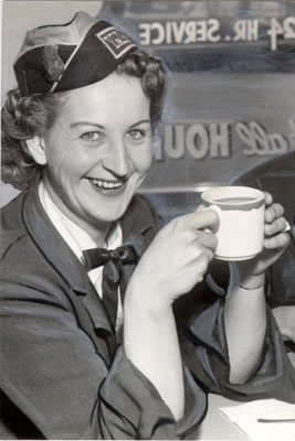 A uniformed woman taxi driver smiles at the camera in 1958, link to a taxi unions article on Taxi Library