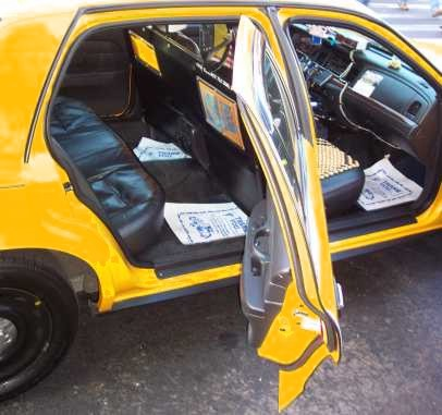 Photo of a yellow cab with open doors and a partition