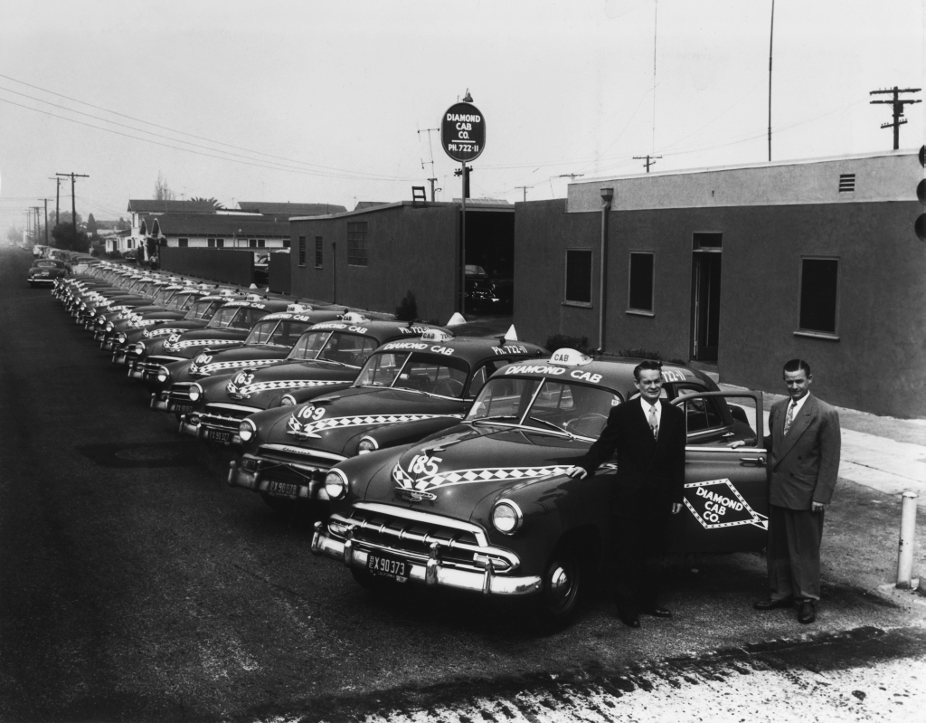 Diamond Cab executives pose alongside a row of about twenty parked taxicabs
