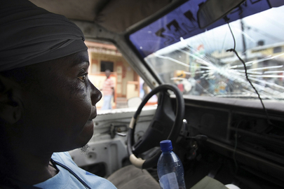 A woman passenger rides in a shared taxi. The taxi's windshield is damaged and the woman has an anxious expression on her face.