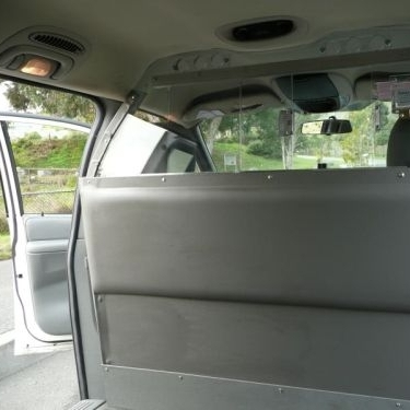 Photo of a bullet-resistant partition in a minivan taxicab; click to read about a Covid-19 taxi design