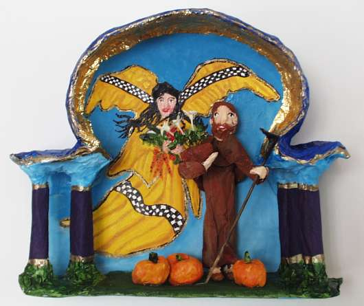 Papier-mache showing St. Fiacre in a garden with an angel hovering nearby. The angel has a taxi-like checkered design on her robes and wings.