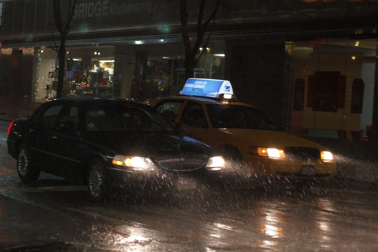 A night scene of a black town car and a yellow taxicab next to each other on a rain soaked street